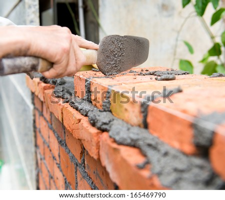 builder laying bricks in site.