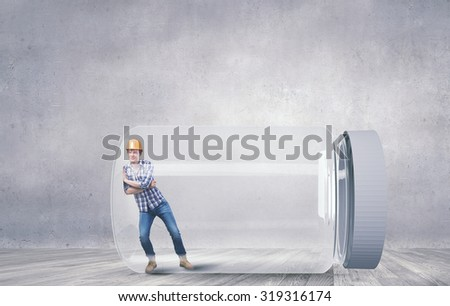 Builder man trapped in glass jar trying to escape - stock photo