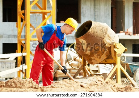 builder man working with shovel during concrete cement solution mortar preparation in mixer at construction site - stock photo