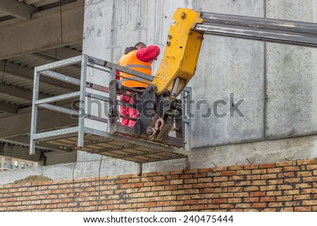 Builder on aerial access platform at construction site.