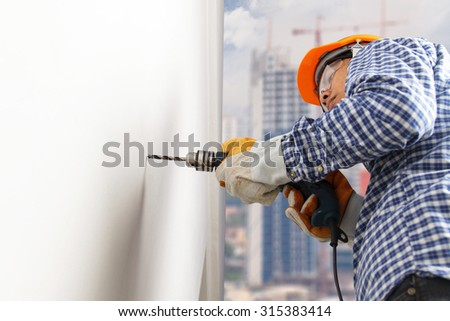 Builder or worker drilling with a machine or drill - stock photo