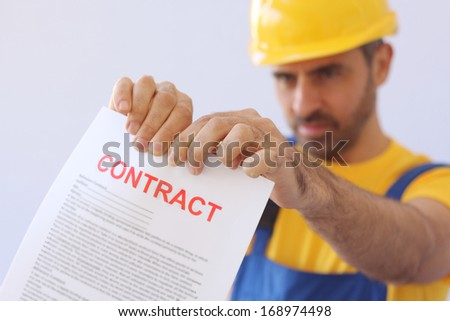 Builder or workman in a safety helmet ripping up a contract which he is holding extended in front of him with focus to the document - stock photo