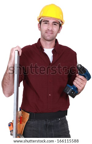 Builder posing with drill and plank - stock photo