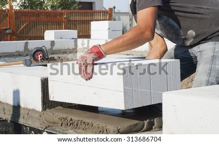 builder puts on grout aerated concrete block