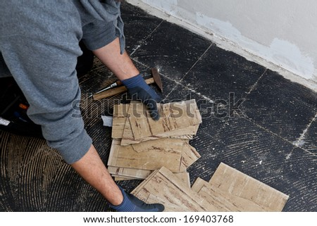 Builder removing damaged floor tiles with his gloved hands during renovations on a building so that he cam install new flooring - stock photo