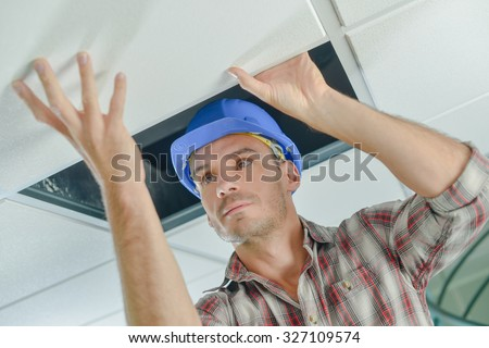 Builder replacing ceiling panel - stock photo