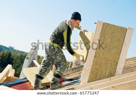 builder roofer working with insulation material at construction works - stock photo