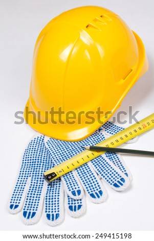 builder's tools - yellow helmet, work gloves, pen and measure tape  over white background - stock photo