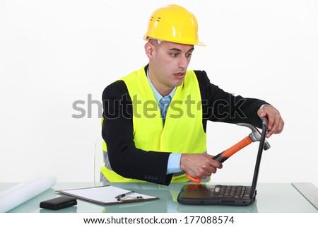 Builder smashing laptop screen - stock photo