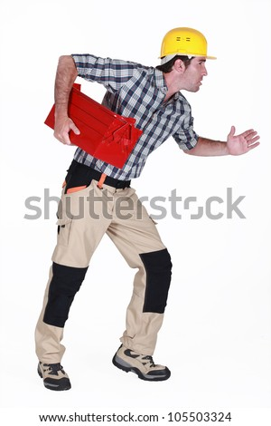 Builder stood in running position holding tool box - stock photo