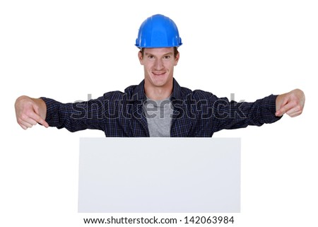 Builder stood pointing at large billboard - stock photo