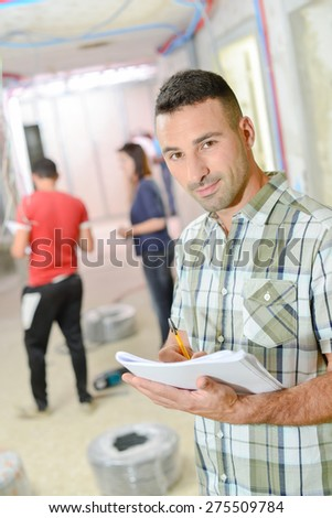 Builder taking notes as he works - stock photo