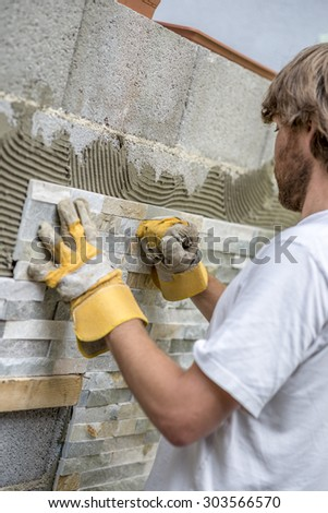 Builder tiling a wall with ornamental tiles pushing the tile into the cement on the wall with his gloved fist in a DIY, renovation or construction concept - stock photo