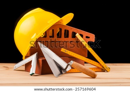 builder  tools on black background and wooden table - stock photo