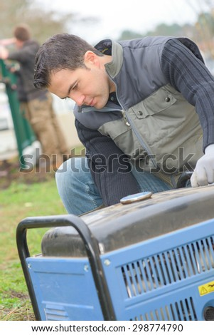 Builder turning on a mobile generator - stock photo