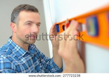 Builder using a spirit level - stock photo