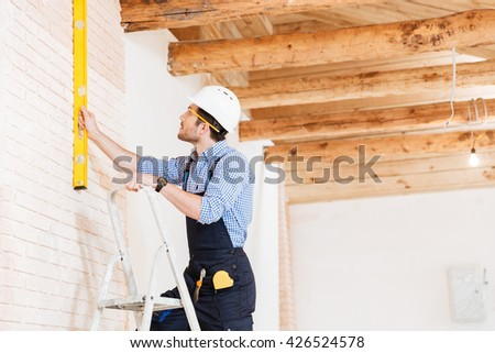 Builder using consruction level and standing n the ladder at the working area - stock photo