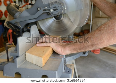 Builder Using Saw to Cut Wood in Shop - stock photo