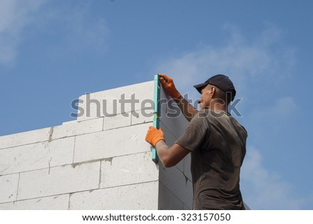 Builder verifies the accuracy of aerated concrete masonry walls - stock photo