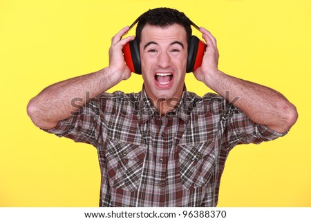 Builder wearing hearing protection - stock photo