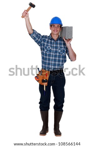 Builder with a block and hammer - stock photo
