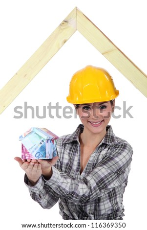 Builder with a house made of money - stock photo