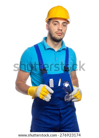 Builder with crossed arms in a protective blue clothing isolated on white background. Young construction worker wearing hardhat or yellow helmet.