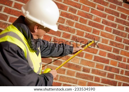 Builder With Tape Measure - stock photo
