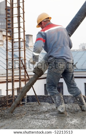 builder worker aiming pump tube during concrete pouring process