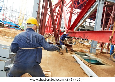 builder worker at construction site installing metal construction frames - stock photo