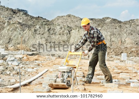 builder worker at outdoor sand ground compaction with vibration plate compactor machine before concrete filling