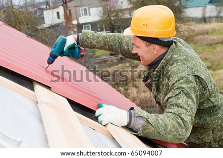 builder worker at roofing works on metal tiling with screwdriver