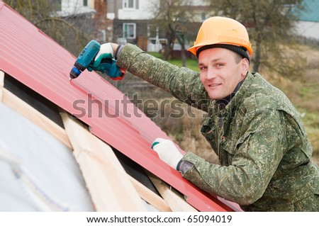 builder worker at roofing works on metal tiling with screwdriver - stock photo