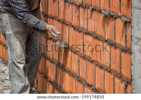 Builder worker, clay block wall and trowel. Builder worker using the sharp end of the trowel, scrape off any excess mortar that spreads beyond the joint. Selective focus and motion blur. - stock photo