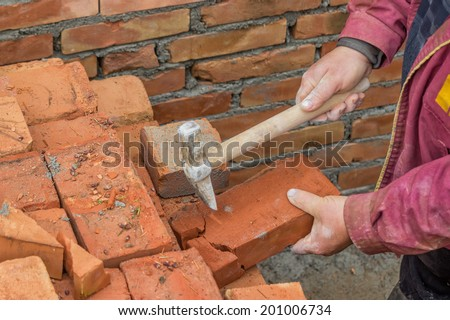 Builder worker cutting a brick. worker need plenty of half bricks to break the bond. Selective focus and motion blur.