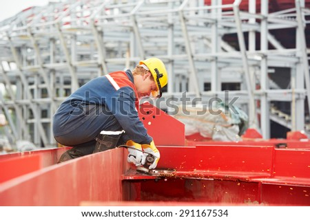 builder worker in safety protective equipment smothing out welded joint at metal construction frame by grinding machine - stock photo