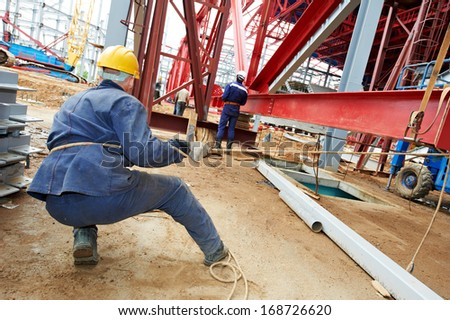 builder worker in uniform at construction site installing metal construction frames - stock photo