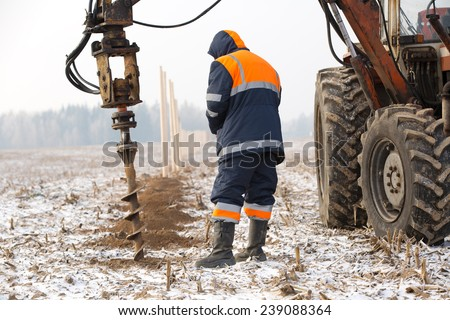 Builder worker monitoring boring holes in ground with drilling rig during fence construction - stock photo