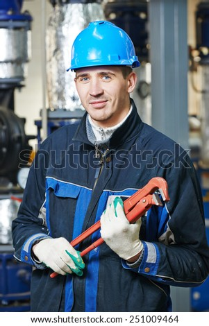 builder worker painting facade of high-rise building with roller - stock photo