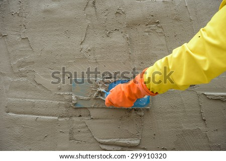 Builder worker plastering  concrete at wall - stock photo