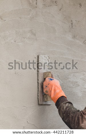 Builder worker plastering concrete  at wall of house construction - stock photo