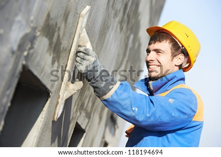 builder worker plastering facade industrial building with putty knife float - stock photo