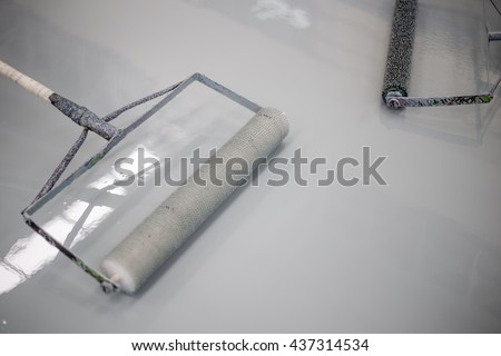Builder worker use a roller paint epoxy at floor new factory   - stock photo