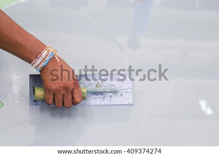 Builder worker use a trowel paint epoxy at floor new factory  - stock photo