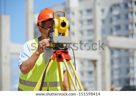 builder worker with theodolite transit equipment at construction site outdoors during surveyor work - stock photo