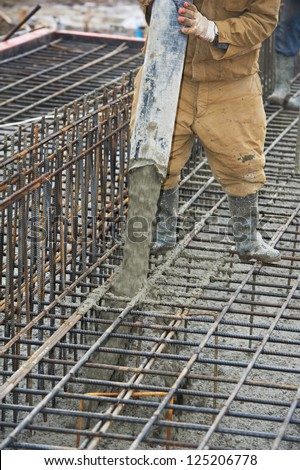 builder worker with tube from truck mounted concrete pump pouring cement into formwork reinforcement - stock photo