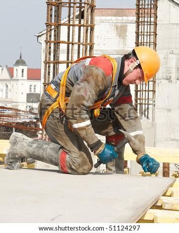 builder working in protective wear, helmet and equipment - stock photo