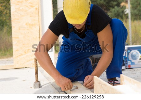 Builder working on a construction site kneeling down fitting a bolt to in insulated wooden beam in his hardhat and overalls - stock photo