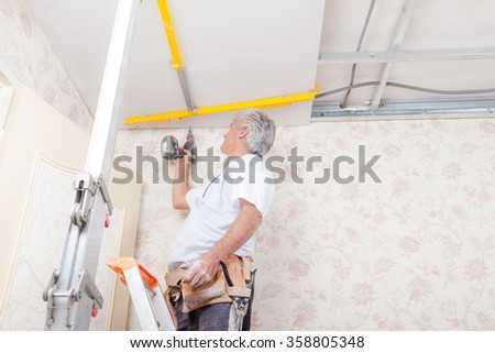 Builder working on ceiling - stock photo