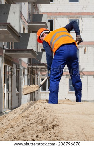 Builder working using shovel at construction site - stock photo